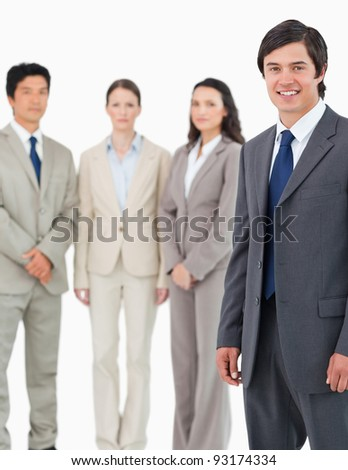 Smiling young salesman with his team behind him against a white background