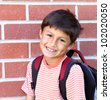 Smiling young schoolboy with backpack gets ready to enter school. - stock photo