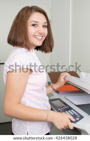 Smiling young secretary using a copy machine - stock photo