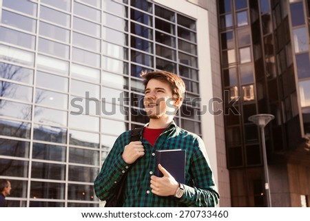 Smiling young student man holding a book and a bag on a university background .Young smiling student  outdoors Life style.City.Student. - stock photo