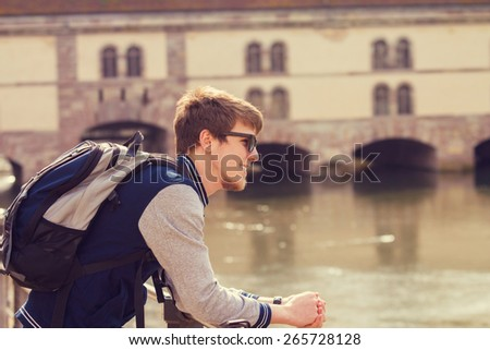 Smiling young student relaxing near to a river.Thinking student,Relaxing,Outdoors.Park. - stock photo