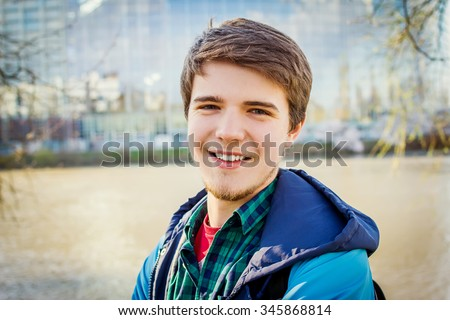 Smiling young student relaxing.University.Smiling young student man holding a bag in sunrise near river. - stock photo