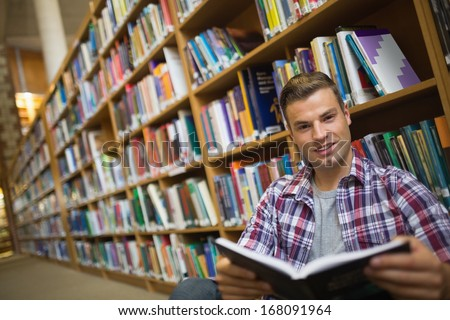 Smiling young student sitting on library floor reading book in college
