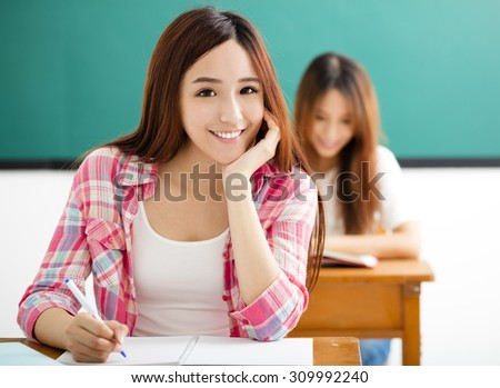smiling Young  student with others  in the classroom - stock photo