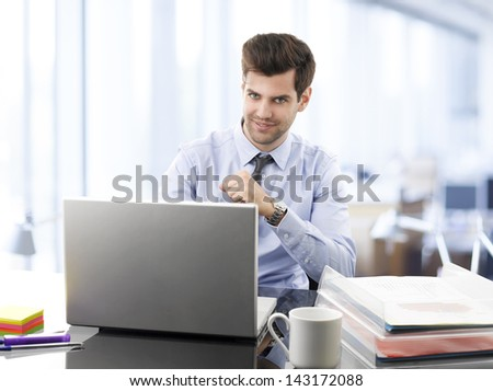Smiling, young, successful businessman working on laptop in office.