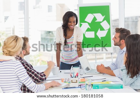 Smiling young team having a meeting about recycling policy in creative office - stock photo