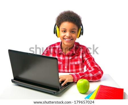 Smiling young teenager, school boy surfing internet. Handsome African American student with headset working at computer. Isolated, over white background, with copy space. - stock photo