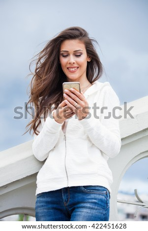 smiling young urban girl with smartphone in blue jeans and white sweater  on stairs summer day in city