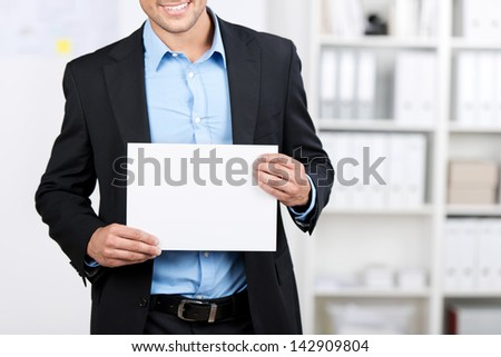 Smiling young well dressed businessman showing a blank sheet.