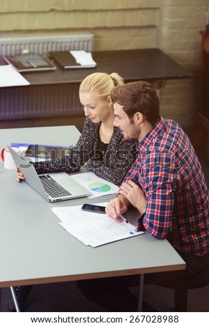 Smiling Young White Couple Looking at the Screen of the Laptop Computer on Top of a Gray Table with Documents. - stock photo
