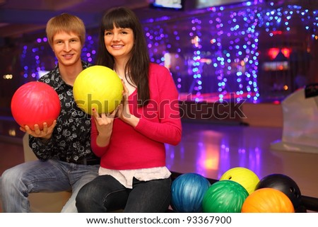 smiling young wife and husband with red and yellow balls sit in bowling club - stock photo