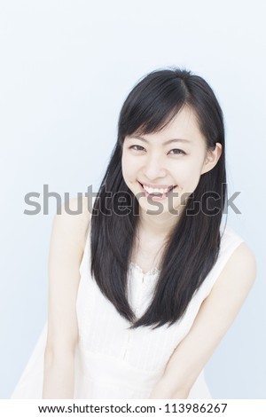 smiling young woman against pale blue background