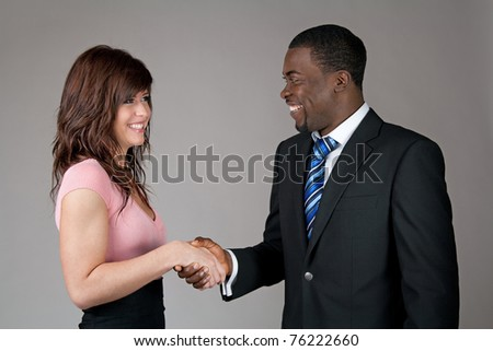 Smiling young woman and African American business man shaking hands. - stock photo
