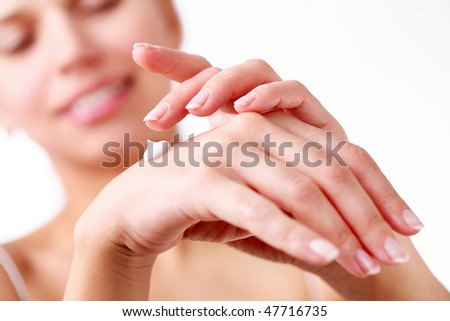 Smiling young woman applies cream on her hands. On a white background. - stock photo