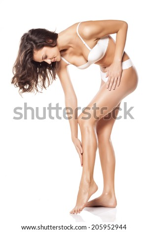 smiling young woman apply lotion on her legs - stock photo