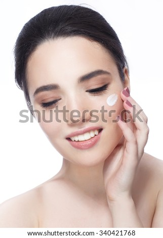 Smiling young woman applying face cream, close eyes - stock photo
