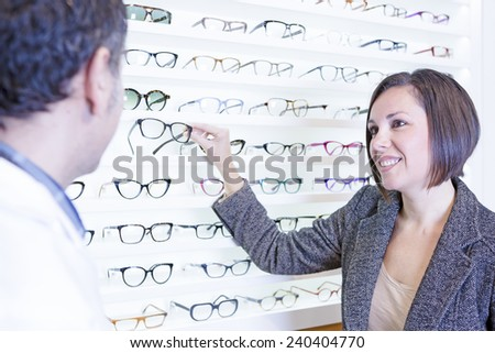 smiling young woman asking for advice to the optician and choosing glasses at the optical store - focus on the woman eyes - stock photo