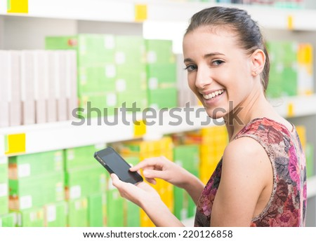 Smiling young woman at supermarket using mobile phone and looking at camera. - stock photo