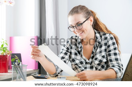 Smiling young woman calculating and paying bills in home office