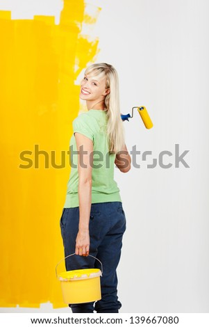 Smiling young woman carrying yellow paint in a container and a roller in her hand turning back to look at the camera as she prepares to continue decorating her house
