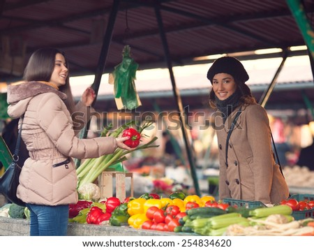 Smiling young woman choosing vegetables at the market place - stock photo