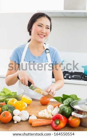 Smiling young woman chopping vegetables in the kitchen at home
