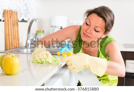 Smiling young woman cleaning furniture in kitchen at home
