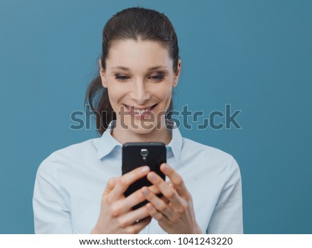 Smiling young woman connecting with her smartphone and social networking