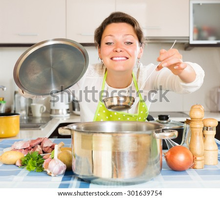 Smiling young woman cooking soup with meat and vegetables at home - stock photo