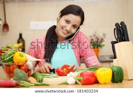 Smiling young woman cutting vegetables and talking on cellphone