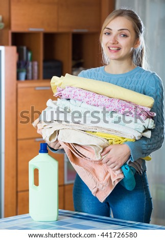 Smiling young woman doing laundry in domestic interior - stock photo