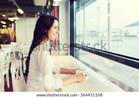 smiling young woman drinking coffee at cafe - stock photo