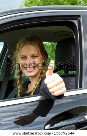 Smiling  young woman drive a car and looking at camera with thumb up - stock photo