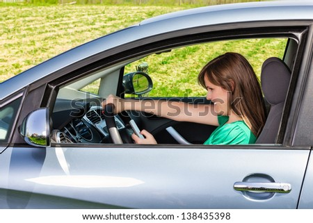 Smiling young woman driver reading/typing a text message on her mobil phone - stock photo
