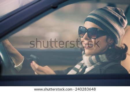 Smiling young woman driving a car and using mobile phone - stock photo