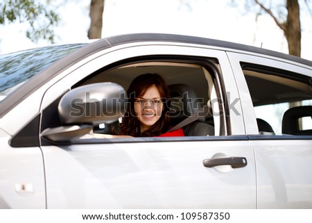Smiling young woman driving her new, modern car