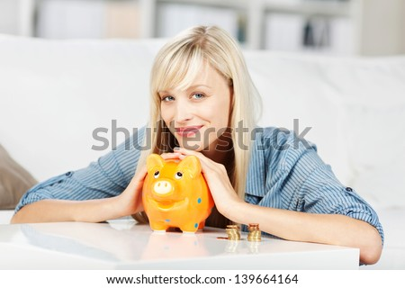 Smiling young woman dropping coins on her piggybank