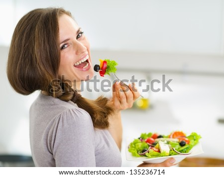 Smiling young woman eating fresh salad in modern kitchen - stock photo