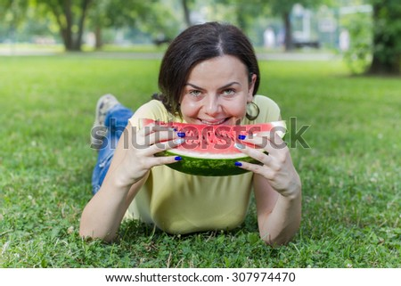 Smiling Young Woman Eating Fresh Watermelon at beautiful summer day in the park.   - stock photo