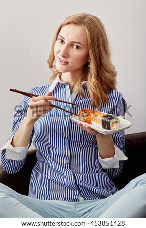 smiling young woman eating sushi on white background - stock photo