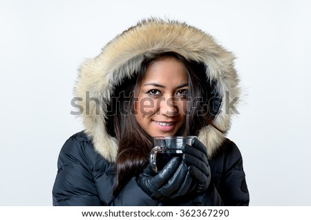 Smiling young woman enjoying a hot beverage clasping the mug in her gloved hands as she cuddles down in her warm furry hood to keep warm in winter - stock photo