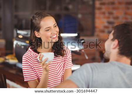 Smiling young woman enjoying coffee with a friend at coffee shop