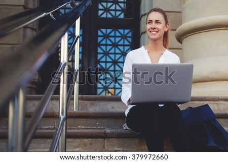 Smiling young woman enjoying good day while sitting with open net-book on stairs of architectural monument, happy female traveler enjoying architecture of city during work on laptop computer outside - stock photo