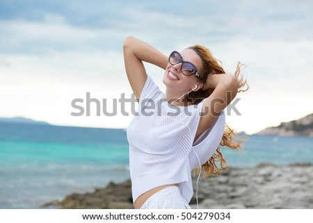 Smiling young woman enjoying her summer vacation on the beach. Beautiful female model in sunglasses having fun on the sea shore.