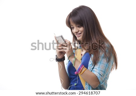 Smiling young woman enjoying music over white background