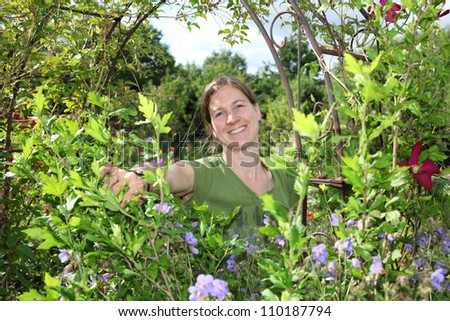 Smiling young woman enjoys her garden