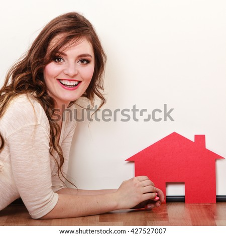 Smiling young woman girl holding paper house dreaming about new home. Housing and real estate concept.