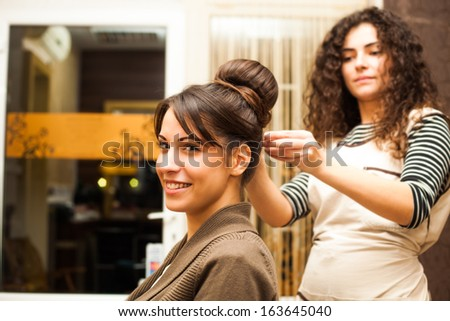 smiling young woman hairdo at hairdressing salon - stock photo