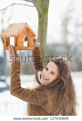 Smiling young woman hanging bird feeder on tree in winter outdoors - stock photo