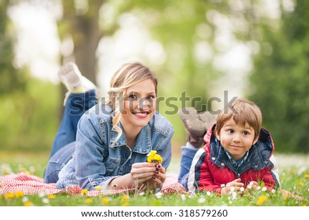 Smiling young woman having a picnic with her cute little son - stock photo